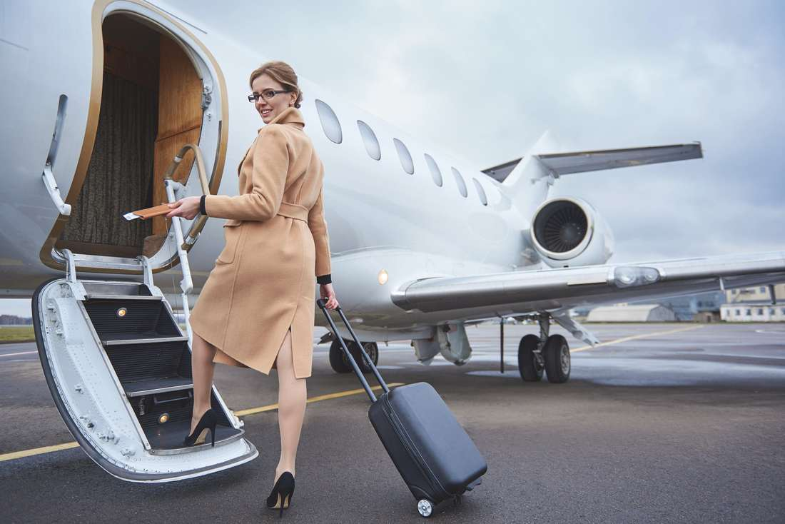 Full length portrait of happy female holding cards and baggage while boarding a plane