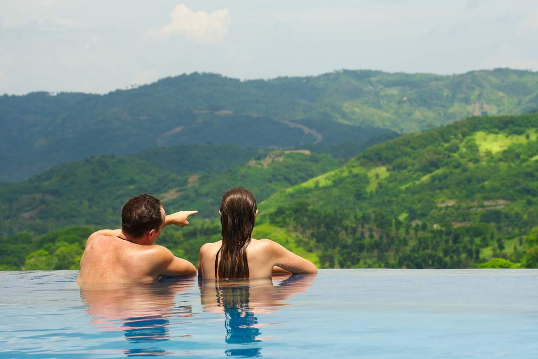 Rear view of happy couple in the luxury pool looking at mountain landscape